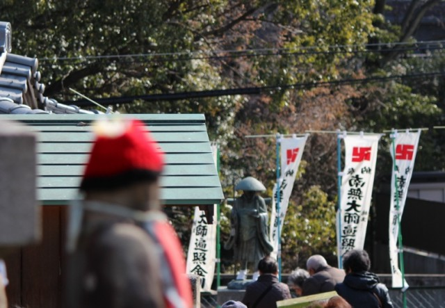 山門手前の隅っこに弘法大師像が -覚王山 日泰寺参道の縁日-